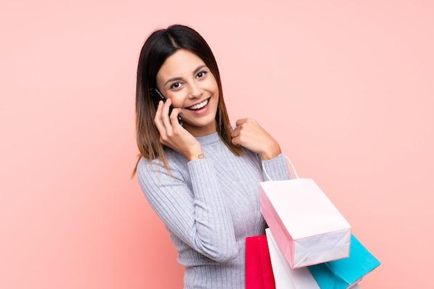 Mujer sobre pared rosa sosteniendo bolsas de compras y llamando a un amigo con su teléfono celular