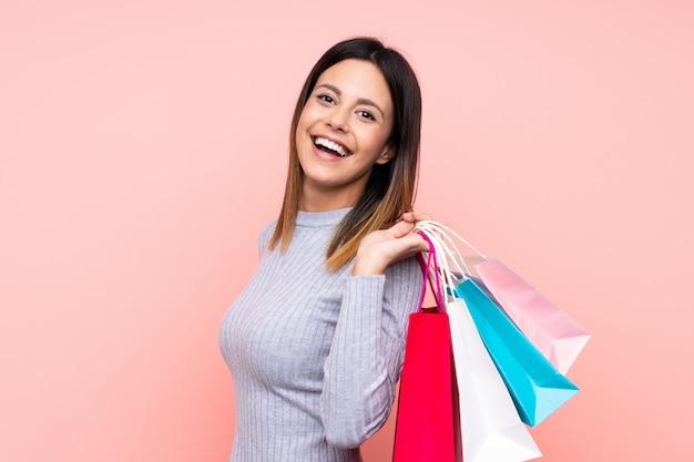 Mujer sobre pared rosa sosteniendo bolsas de compras y sonriendo