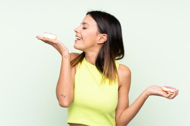 Mujer sobre pared verde con donas con expresión feliz