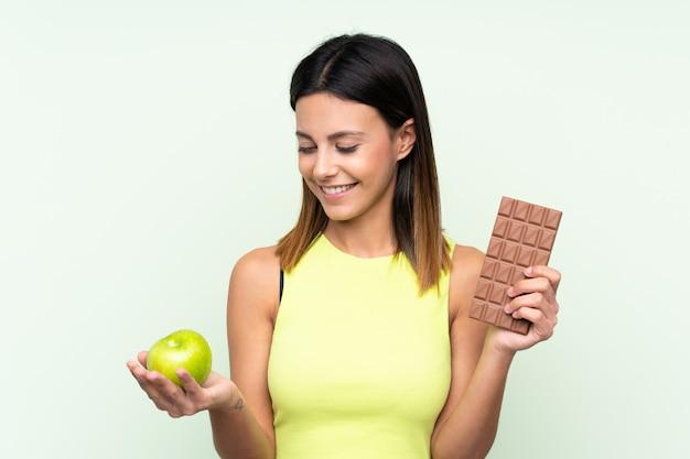 Mujer sobre pared verde tomando una tableta de chocolate en una mano y una manzana en la otra