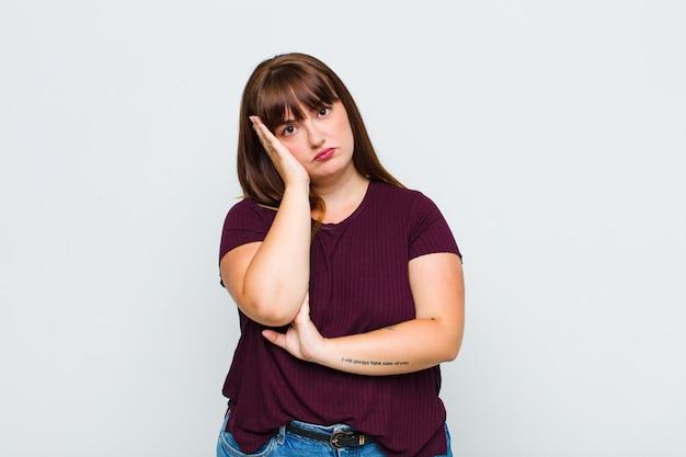 Mujer con sobrepeso que se siente aburrida, frustrada y somnolienta después de una tarea aburrida, aburrida y tediosa, sosteniendo la cara con la mano