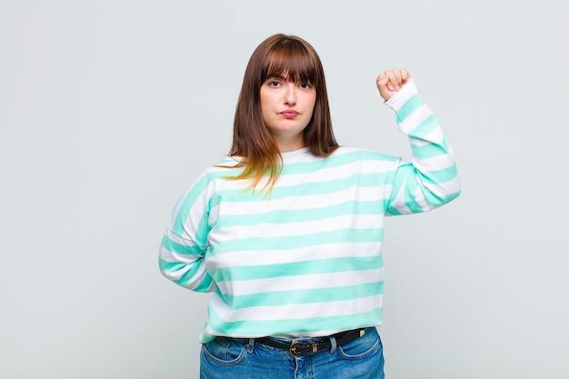 Mujer con sobrepeso que se siente seria, fuerte y rebelde, levanta el puño, protesta o lucha por la revolución