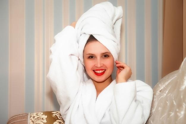 Mujer en el sofá de la habitación del hotel después de la ducha. bonita mujer de apariencia eslava en bata y toalla en la cabeza