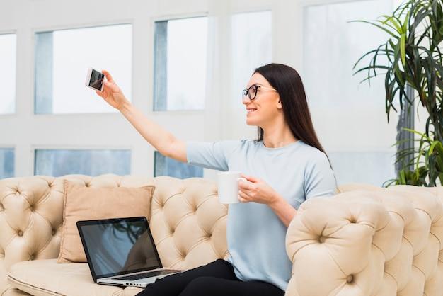 Mujer en sofá tomando selfie con café