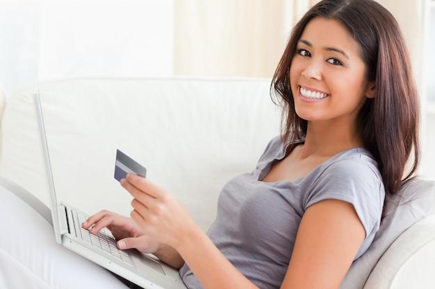 Mujer en el sofá trabajando con el cuaderno sonriendo a la cámara