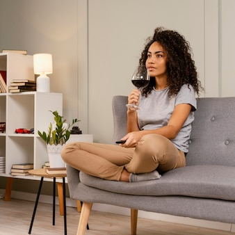 Mujer en el sofá viendo la televisión y bebiendo vino