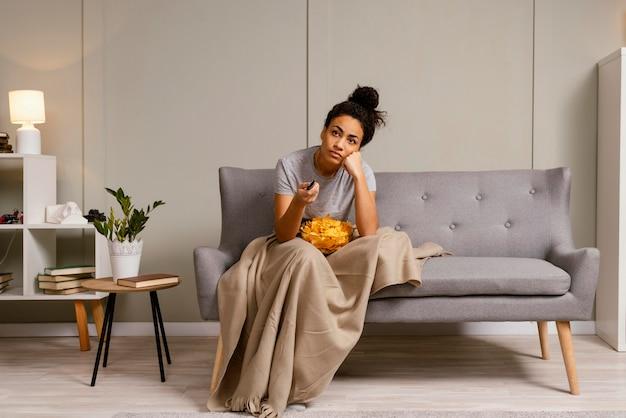 Mujer en el sofá viendo la televisión y comiendo patatas fritas