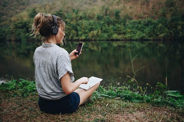 Mujer sola en la naturaleza escuchando música con auriculares, tableta digital y teléfono inteligente