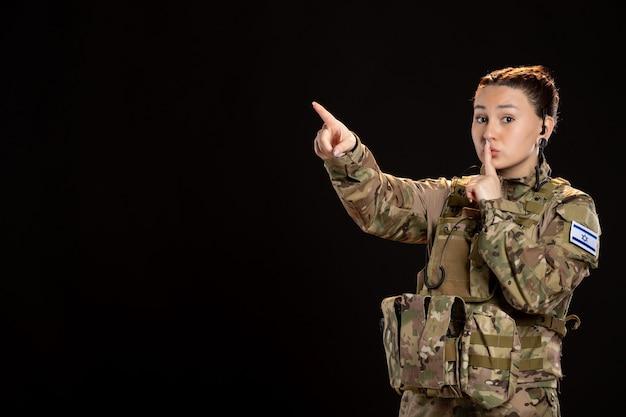 Mujer soldado en camuflaje en la pared negra