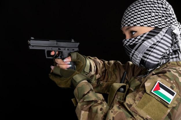 Mujer soldado en camuflaje y shemagh apuntando con pistola sobre pared negra