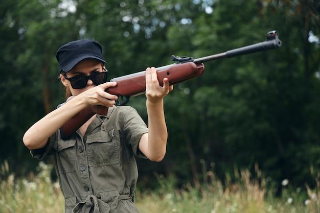 Mujer soldado con gafas de sol y caza de armas en el bosque