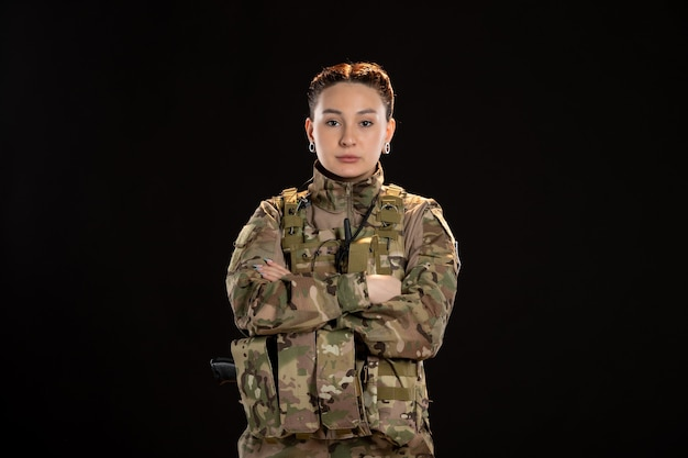 Mujer soldado iin camuflaje en pared negra