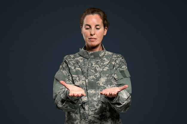 Mujer soldado presentando objeto invisible