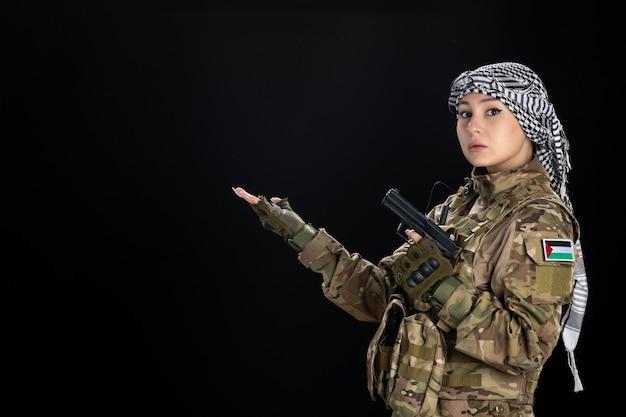 Mujer soldado en uniforme militar con pistola en pared negra