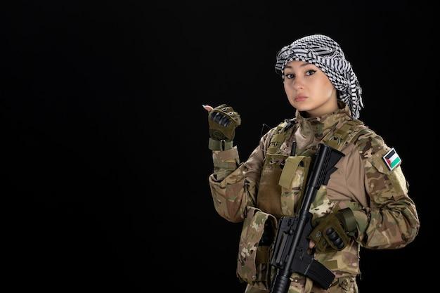 Mujer soldado en uniforme militar con rifle en la pared negra