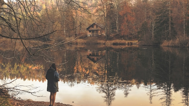 Mujer solitaria de pie cerca del lago con el reflejo de la cabaña de madera aislada visible