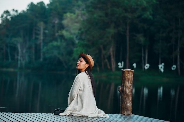 Mujer solitaria sentada en la balsa frente al mar