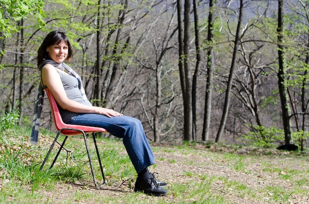 Mujer solitaria sentada en una silla y relajarse en un parque