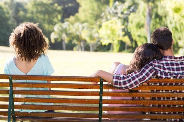 Mujer solitaria, sentado con pareja en el parque