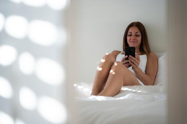 Mujer soltera conectada a su teléfono y comprobar la aplicación de citas.
