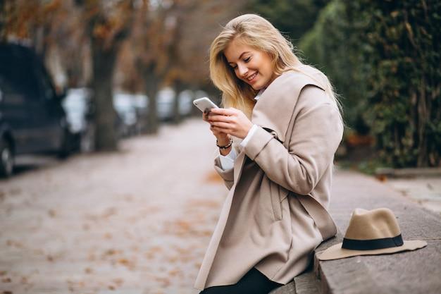 Mujer con sombrero y abrigo en el parque hablando por teléfono