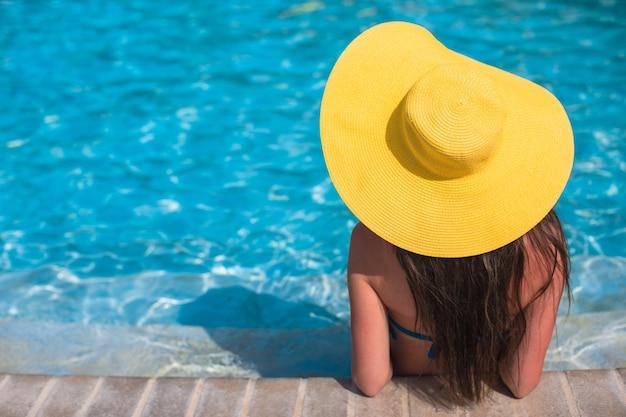 Mujer con sombrero amarillo relajante en la piscina en el exótico resort