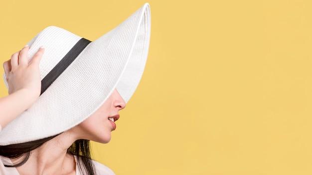Mujer en sombrero blanco sobre fondo amarillo