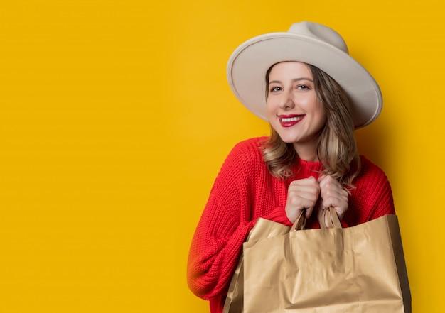 Mujer con sombrero y bolsas de compras