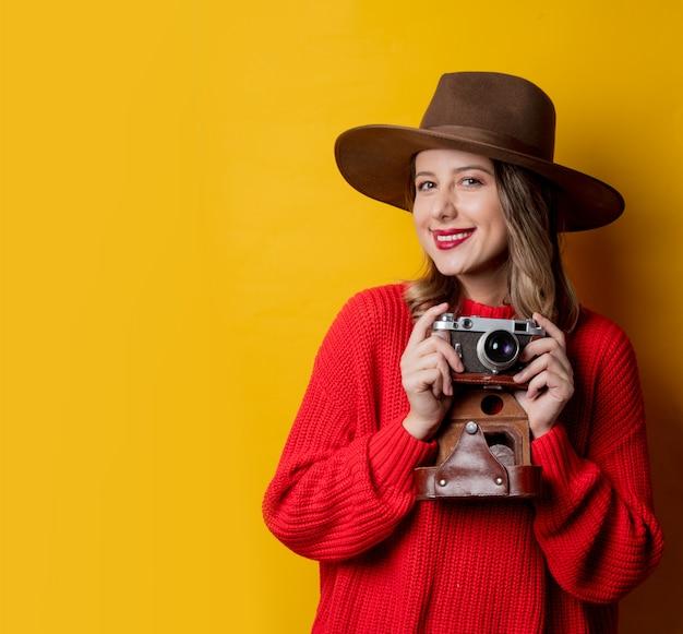 Mujer con sombrero con cámara vintage