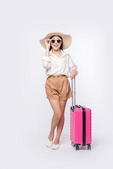 Mujer con sombrero, gafas y asas de maletas para viajar