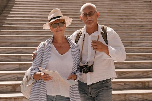 Mujer con sombrero y gafas de sol en blusa a rayas sosteniendo la tarjeta y abrazándose con el hombre con bigote en camisa blanca con cámara