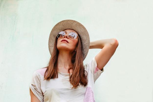 Mujer con sombrero y gafas de sol mirando hacia arriba