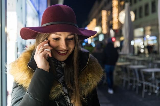 Mujer con sombrero hablando por teléfono en la noche