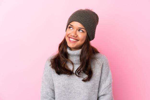 Mujer con sombrero de invierno sobre pared rosa aislado