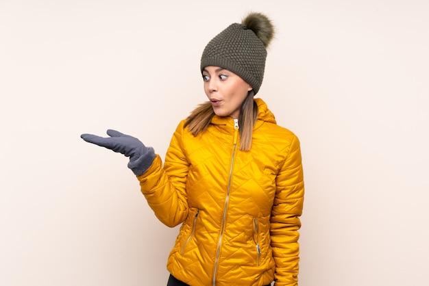 Mujer con sombrero de invierno sobre pared sosteniendo copyspace imaginario en la palma