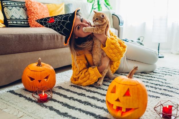 Mujer con sombrero jugando con gato acostado sobre una alfombra decorada con calabazas y velas