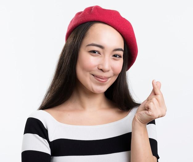 Mujer con sombrero de lectura que muestra el signo del corazón