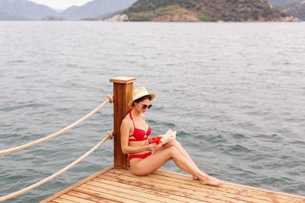 Mujer con sombrero y libro de lectura en el muelle
