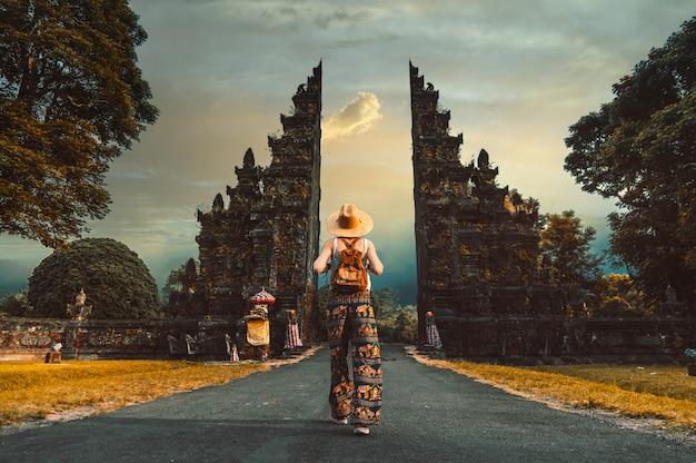 Mujer con sombrero y mochila caminando hacia la entrada del templo hindú en bali, indonesia