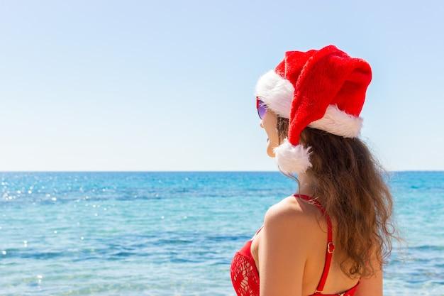 Mujer con sombrero de navidad en la playa.