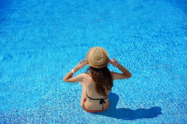 Mujer con sombrero de paja descansando en una tumbona cerca de una lujosa piscina de verano en el hotel