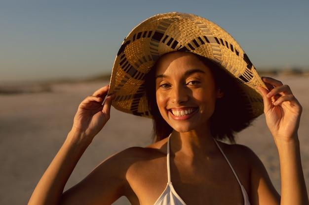 Mujer con sombrero de pie en la playa