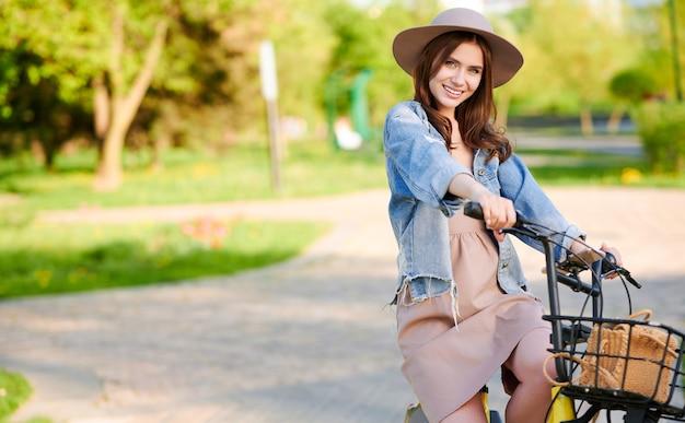 Mujer con sombrero de pie y sonriendo con bicicleta al aire libre en la ciudad de verano