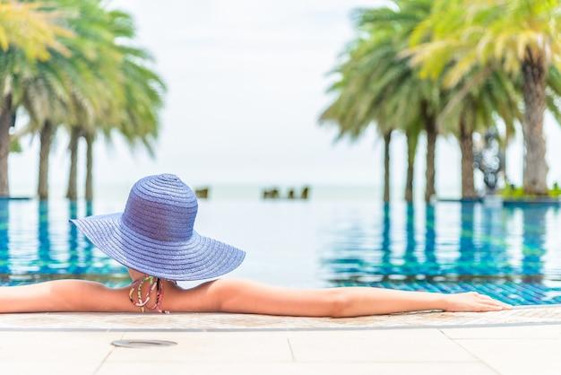 Mujer con sombrero en la piscina del hotel resort