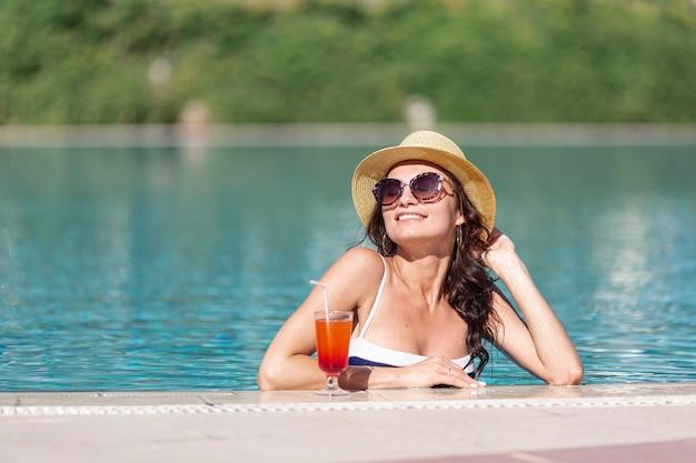 Mujer con sombrero en la piscina