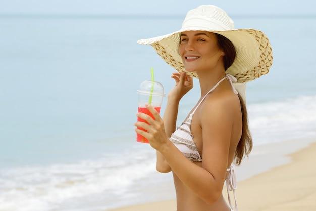 Mujer con sombrero de playa con un cóctel