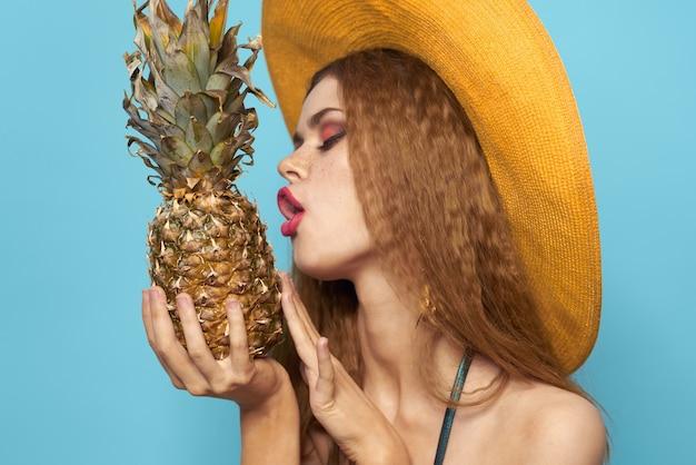 Mujer con sombrero de playa piña con traje de baño frutas exóticas fondo azul vacaciones