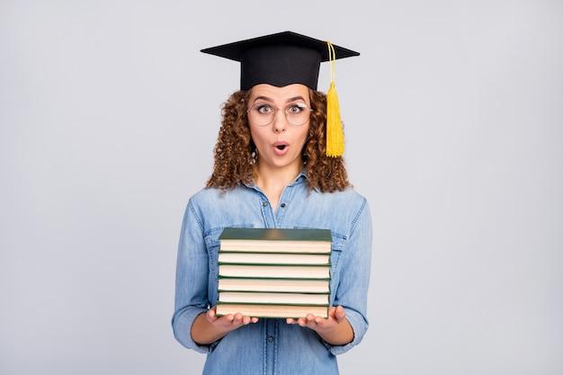 Mujer con sombrero de posgrado y pila de libros