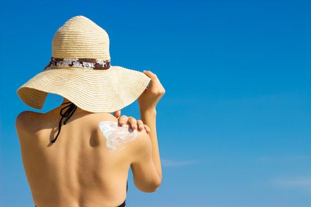 Mujer en un sombrero que aplica protector solar en su hombro