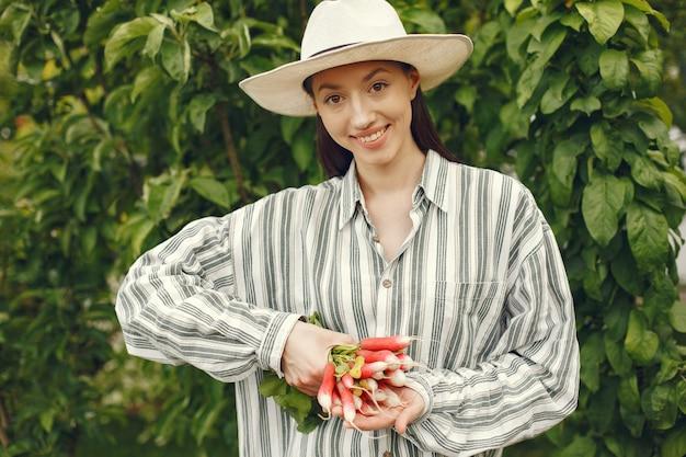 Mujer con un sombrero con rábanos frescos